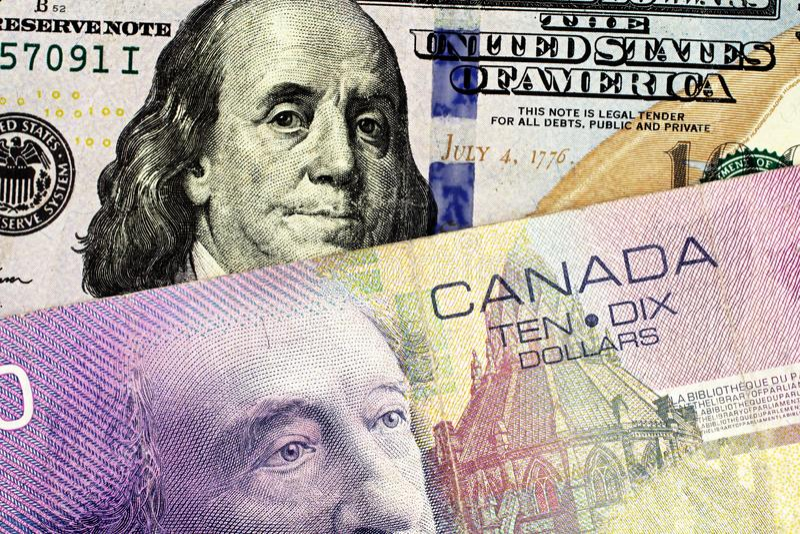 En purpurfärgad kanadensisk räkning för dollar tio med en amerikansk hundra dollarräkning arkivbild
