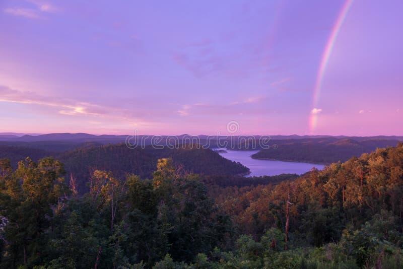 En purpurfärgad kulör himmel med en regnbåge på solnedgången över berg sjön royaltyfri foto