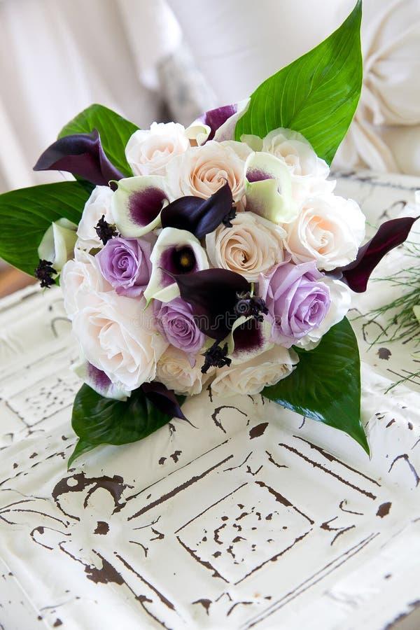 En purpurfärgad och vit bukett av att gifta sig blommor som väntar på en brud arkivfoton
