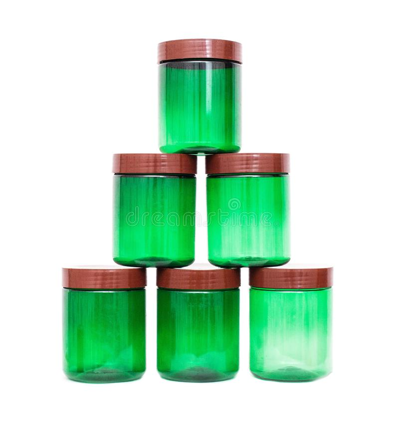 En pyramid av gröna krus för plast- polypropylene på en vit bakgrund, isolat arkivbild