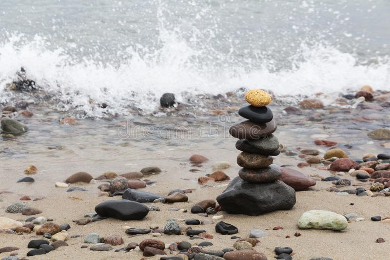 En pyramid av stenar med en ljus sten står upptill på den sandiga stranden Begreppet av ledarskap royaltyfria bilder