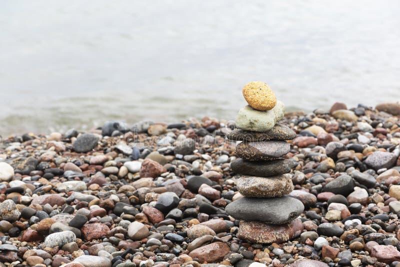 En pyramid av stenar med en ljus sten står upptill på den sandiga stranden Begreppet av ledarskap royaltyfria foton