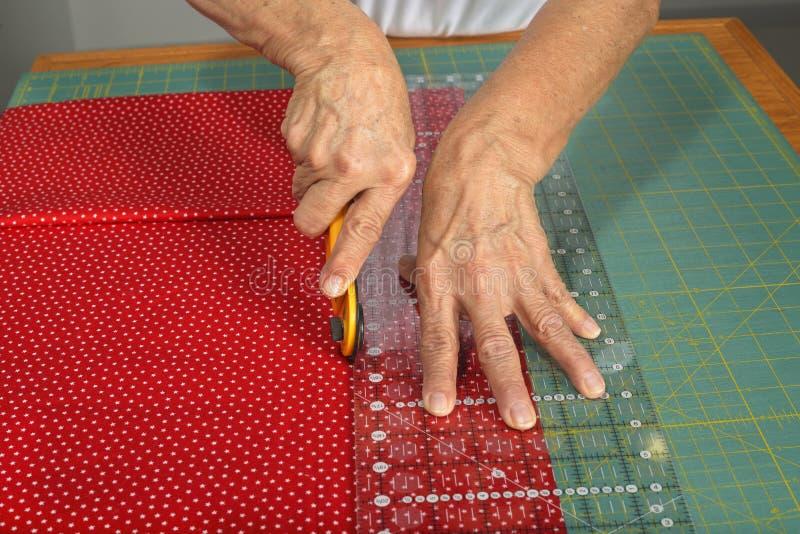 En quilter klipper tyg för täckedanande fotografering för bildbyråer