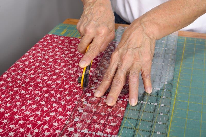En quilter klipper tyg för täckedanande royaltyfri foto