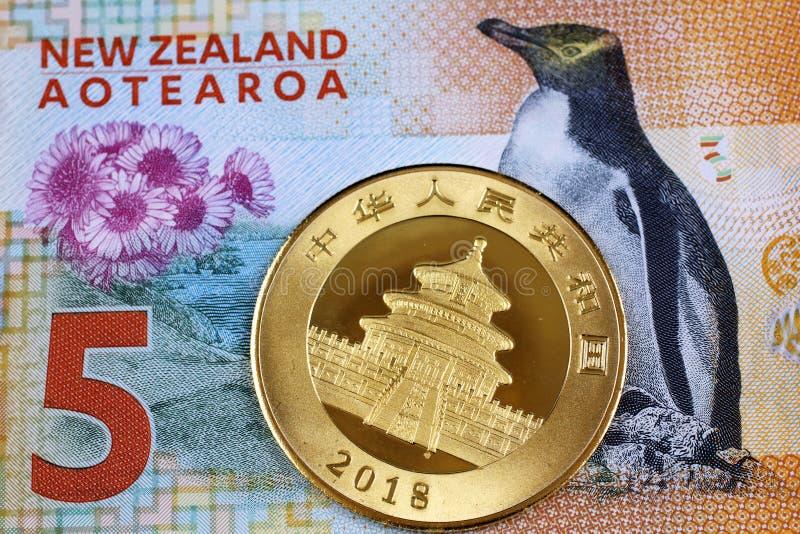 En räkning för nyazeeländsk dollar fem med ett kinesiskt guld- mynt royaltyfri bild