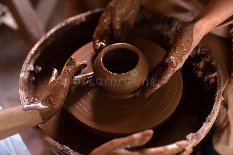 En rå lerakruka i händerna av en keramiker Seminarium i krukmakeriseminariet royaltyfria foton