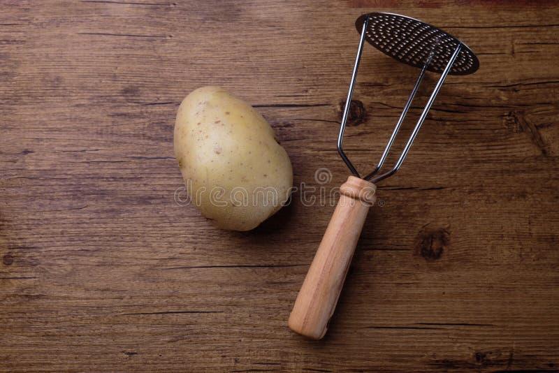 En rå potatoe på en wood tabell med ett hjälpmedel för att krossa fotografering för bildbyråer