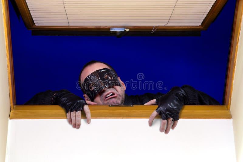 En rånare skriver in huset royaltyfria foton
