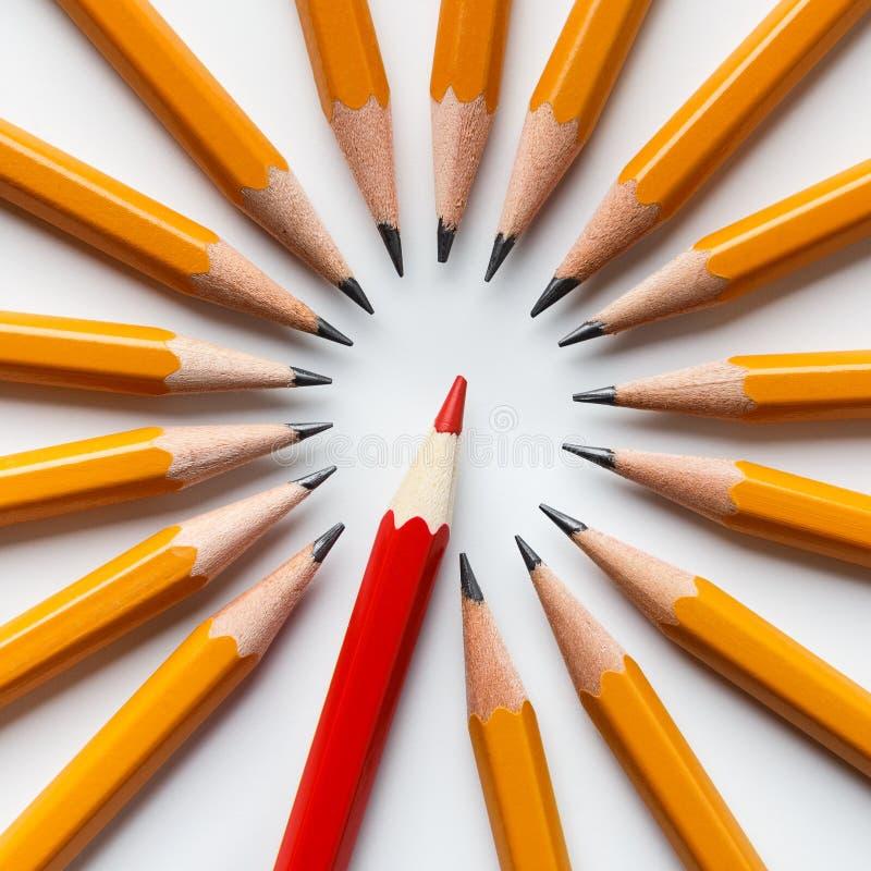 En röd blyertspenna bland gruppen av klassiska gula royaltyfri bild