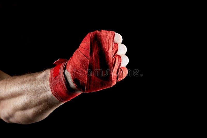 En röd boxare` s förbinder på hans hand som isoleras på mörk suddig bakgrund, närbild arkivfoto