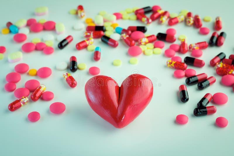 En röd hjärta på färgrika preventivpillerar och injektion arkivbild