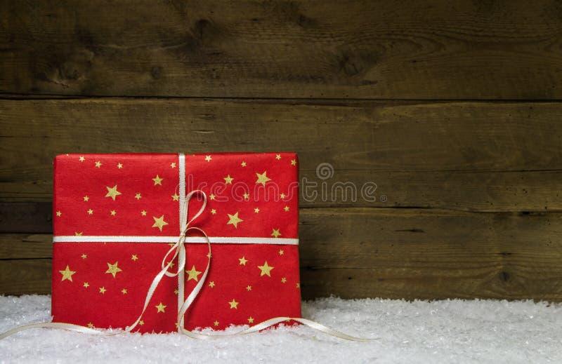 En röd julgåva med guld- stjärnor på träsnöig baksida royaltyfria bilder