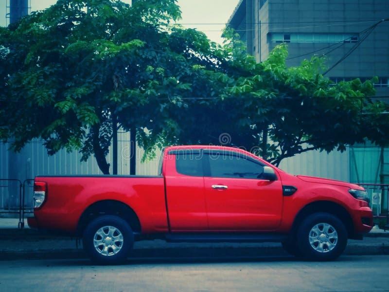 En röd pickup som parkeras bredvid vägen royaltyfria foton
