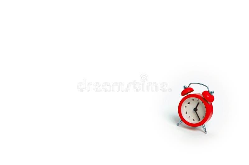 En röd ringklocka på en vit bakgrund Begreppet av tid och planläggningen Forntiden, framtiden och gåvan minimalism fritt royaltyfri foto