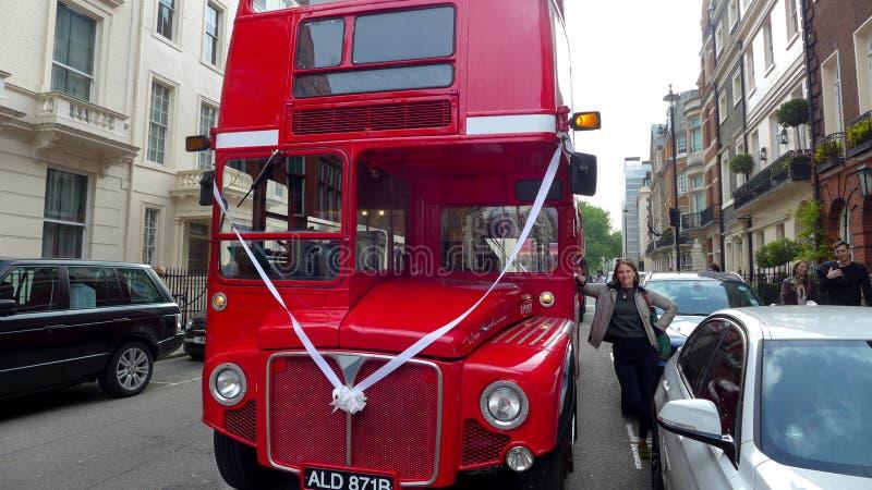 En röd Routemaster buss på en London gata med bandbröllopberöm royaltyfria foton