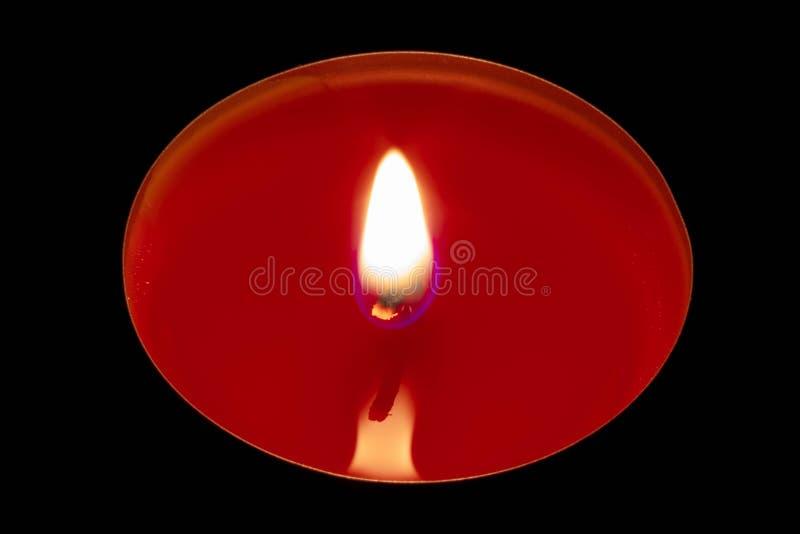 En röd stearinljus på en svart bakgrund arkivfoton