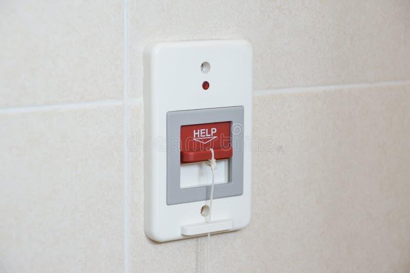 En röd strömbrytare som kallar för nöd- hjälp i toaletten royaltyfri bild