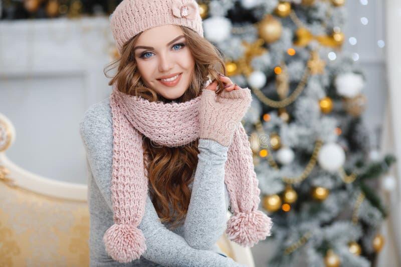 En rödhårig kvinna i den rosa hatten nära julgranen arkivbilder