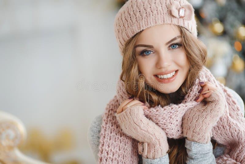 En rödhårig kvinna i den rosa hatten nära julgranen arkivfoto