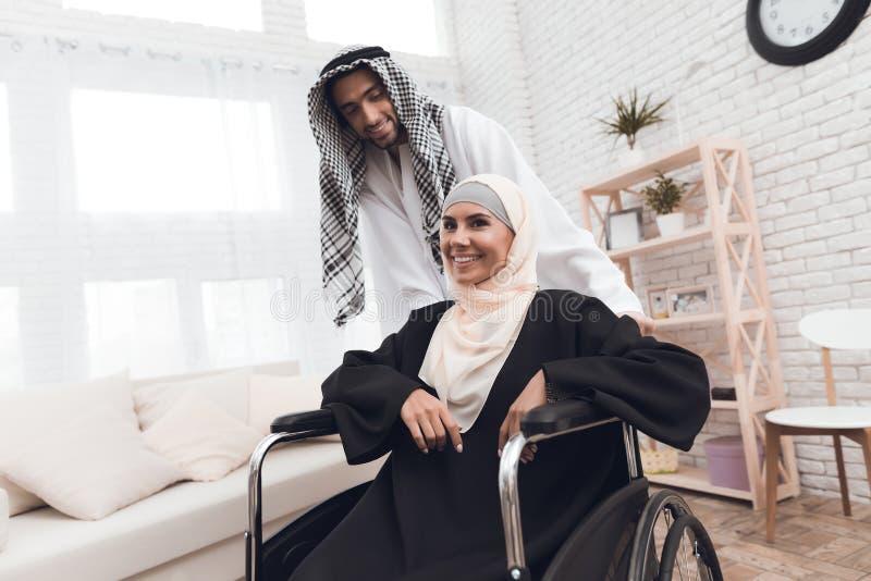 En rörelsehindrad kvinna i en hijab sitter i en rullstol royaltyfri bild