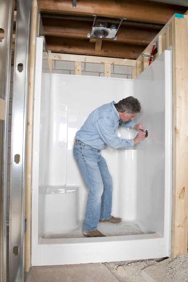 Rörmokaren installerar badrumduschen, hem omdanar royaltyfri bild