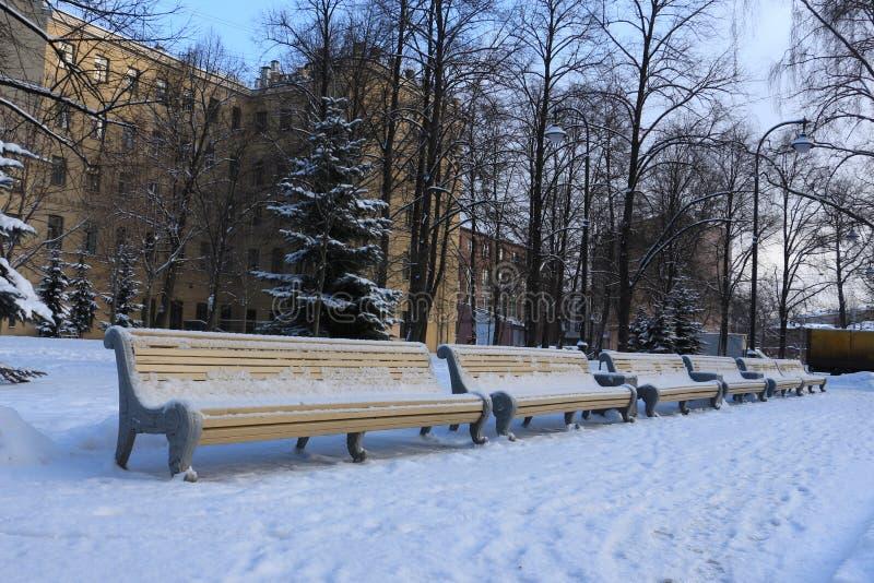 En rad av bänkar i en vinterfyrkant royaltyfria foton