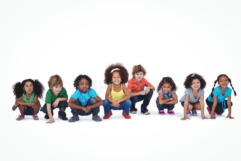 En rad av barn som ner tillsammans huka sig ned arkivfoton