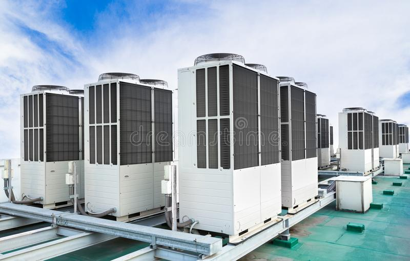 En rad av betingande enheter för luft på tak med blå himmel arkivfoto