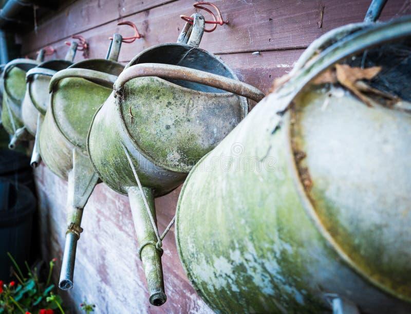 En rad av brunnen använde att bevattna cans hänger på en skjulvägg arkivfoto