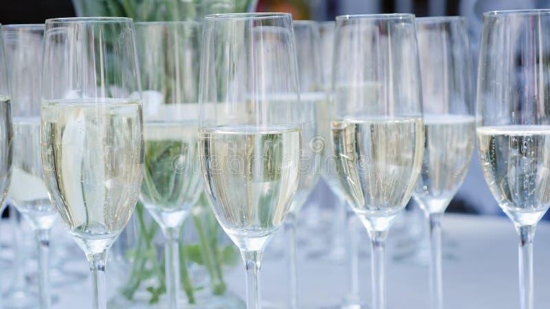 En rad av exponeringsglas som fylls med champagne, är uppställt klart att tjänas som arkivbilder