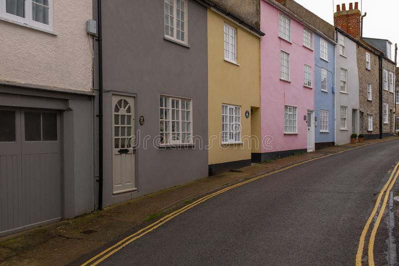 En rad av färgglade hus i en tyst smal gata i Lyme Regis, Dorset, England arkivfoton