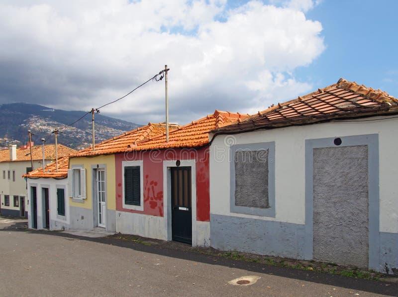 En rad av färgrika gamla målade enkla berättelsehus på en slutta gata i funchal madeira i ljust solljus med blå himmel arkivbilder