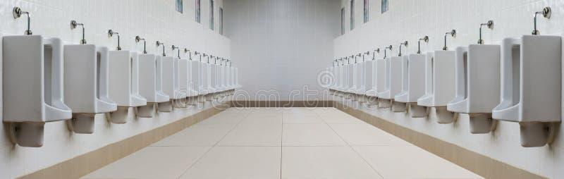 En rad av pissoar i belagd med tegel vägg i en offentlig toalett arkivbilder