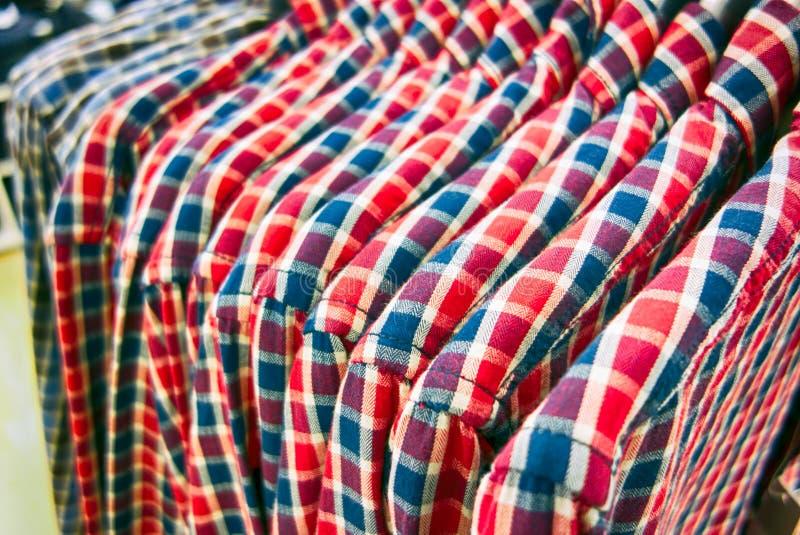 En rad av plädskjortor som hänger på hängare i lager fotografering för bildbyråer