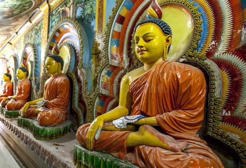 En rad av placerade Buddhastutues inom den Angurukaramulla templet i Negombo i Sri Lanka royaltyfri bild