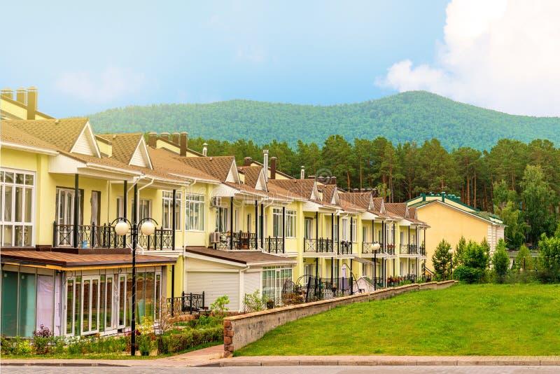 En rad av precis f?rdiga nya gula radhus Bostads- by på foten av bergen royaltyfri fotografi