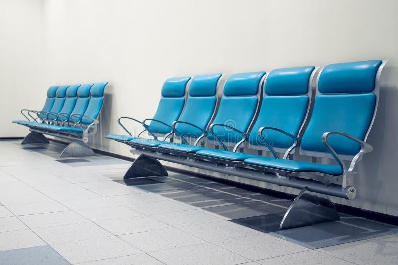 En rad av tomma blåa platser på flygplatsen royaltyfria bilder