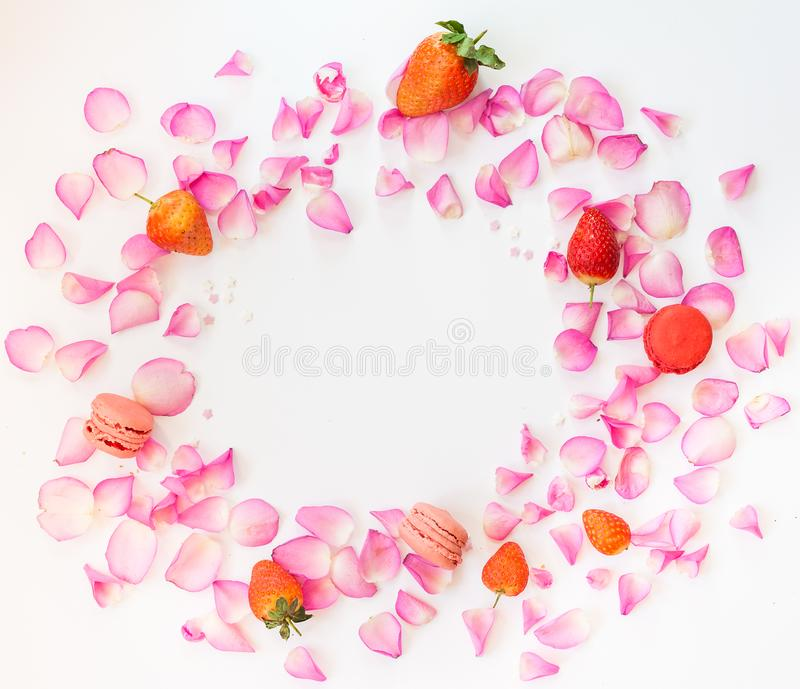 En ram med rosa färgroskronblad, sockerstjärnor, jordgubbar, fransman royaltyfria bilder