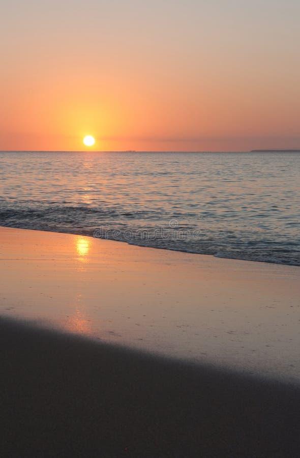 En reflexion av inställningssolen på stranden i Tonga fotografering för bildbyråer