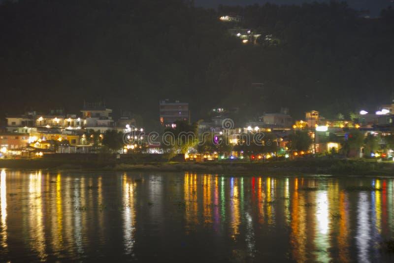 En reflexion av nattstaden i vattnet mot bakgrunden av gröna berg ljusa färgrika banor av ljus på vattnet arkivfoto
