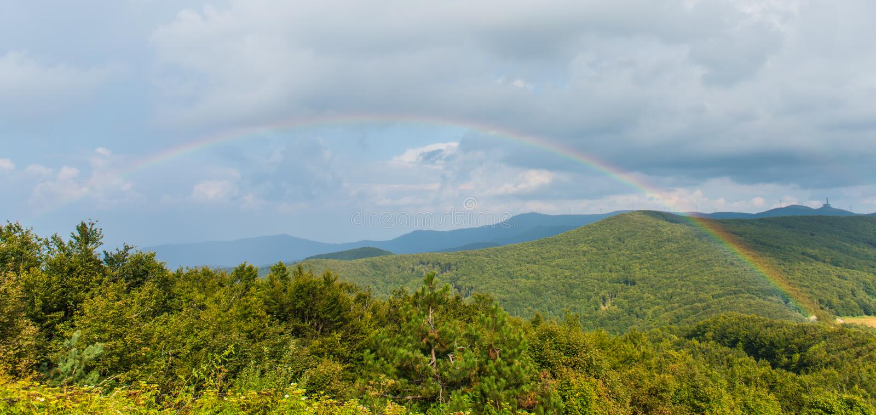 En regnbåge över berget royaltyfri foto