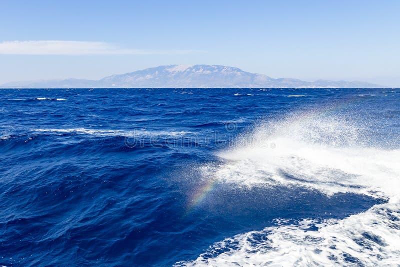 En regnbåge visas i pilbågevågen av fartyget under en tur på havet runt om ön av Zakynthos, Grekland royaltyfria bilder