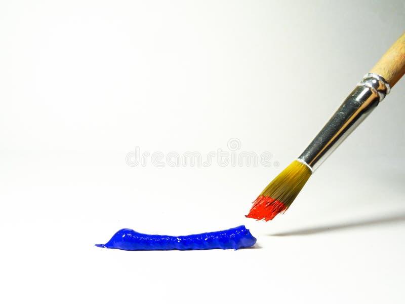 En remsa av blått målar och en borste med röd målarfärg royaltyfria bilder
