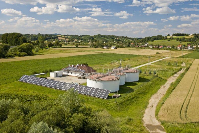 En reningsanläggning i väg från staden bland fälten Sol- celler ackumulerar fri energi Ekologi av bruket av natuen royaltyfria bilder