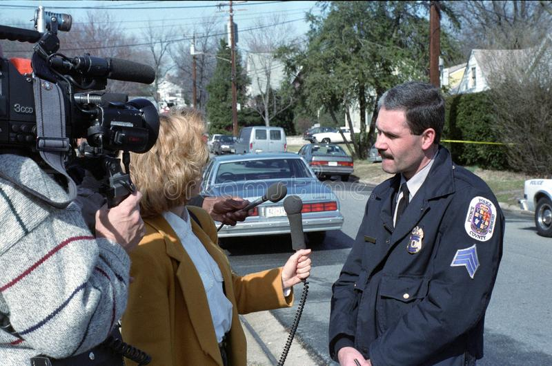 En reporter intervjuar en polis om en händelse arkivfoto