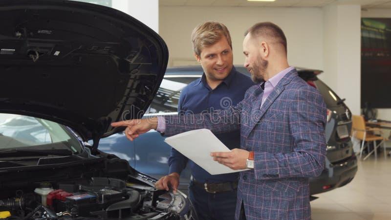 En representativ man väljer den nya bilen i bilsalongen arkivbild