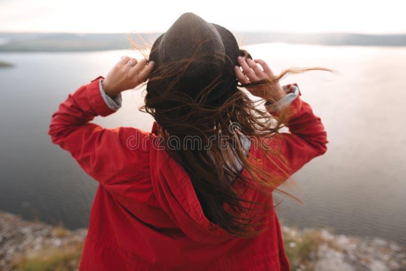 En resande flicka i hatt och med ett blått hår på berget, med vacker solnedgång på floden Ung kvinna i arkivfoto