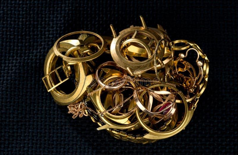 En rest av guld Gamla och brutna smycken, klockor av guld- och guldpläterat på en mörk bakgrund royaltyfria bilder