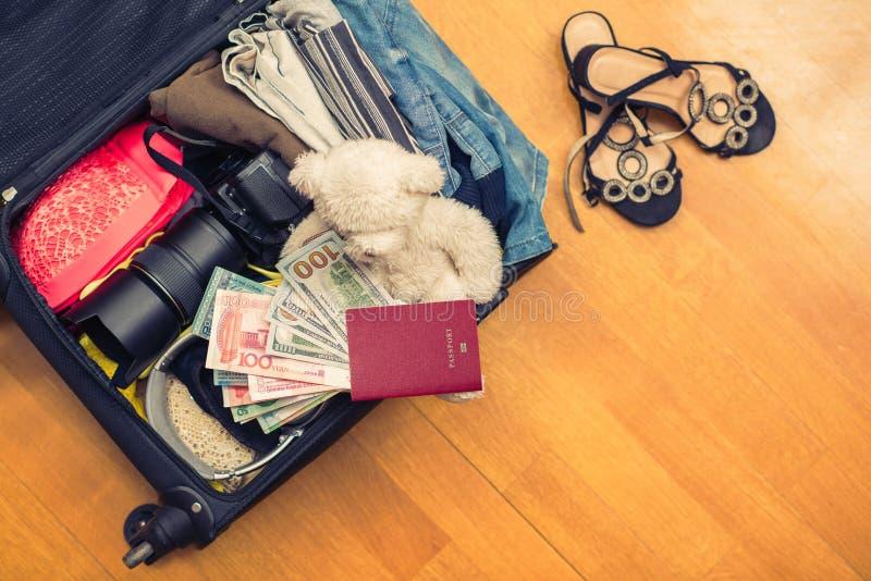 En resväska med sakernallebjörnen och ett utländskt pass Asiatiska pengar- och hundra-dollar räkningar för lopp Begrepp royaltyfria foton