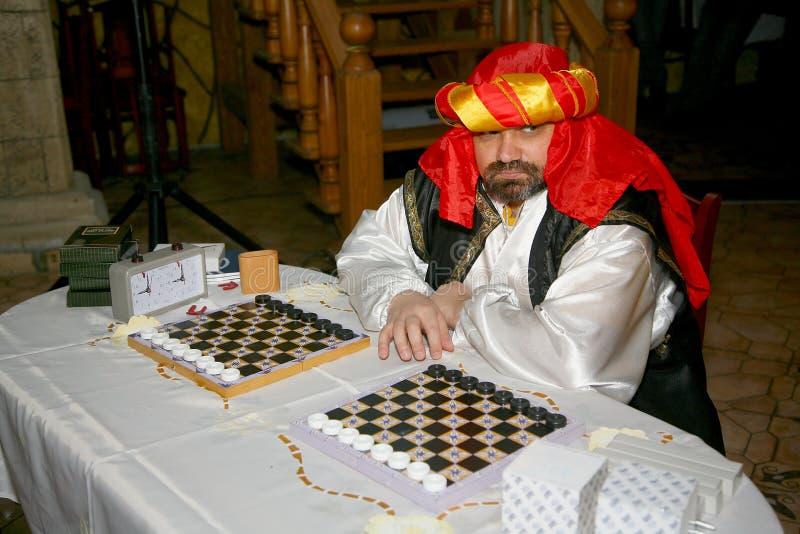 En rik persisk köpman från Bukhara i den östliga dräkten som erbjuder att spela en lek av kontrollörer royaltyfri fotografi